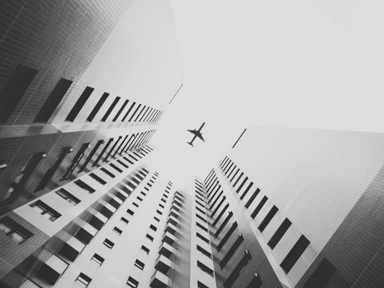 airplane-flying-above-skyscrapers-hd.jpg
