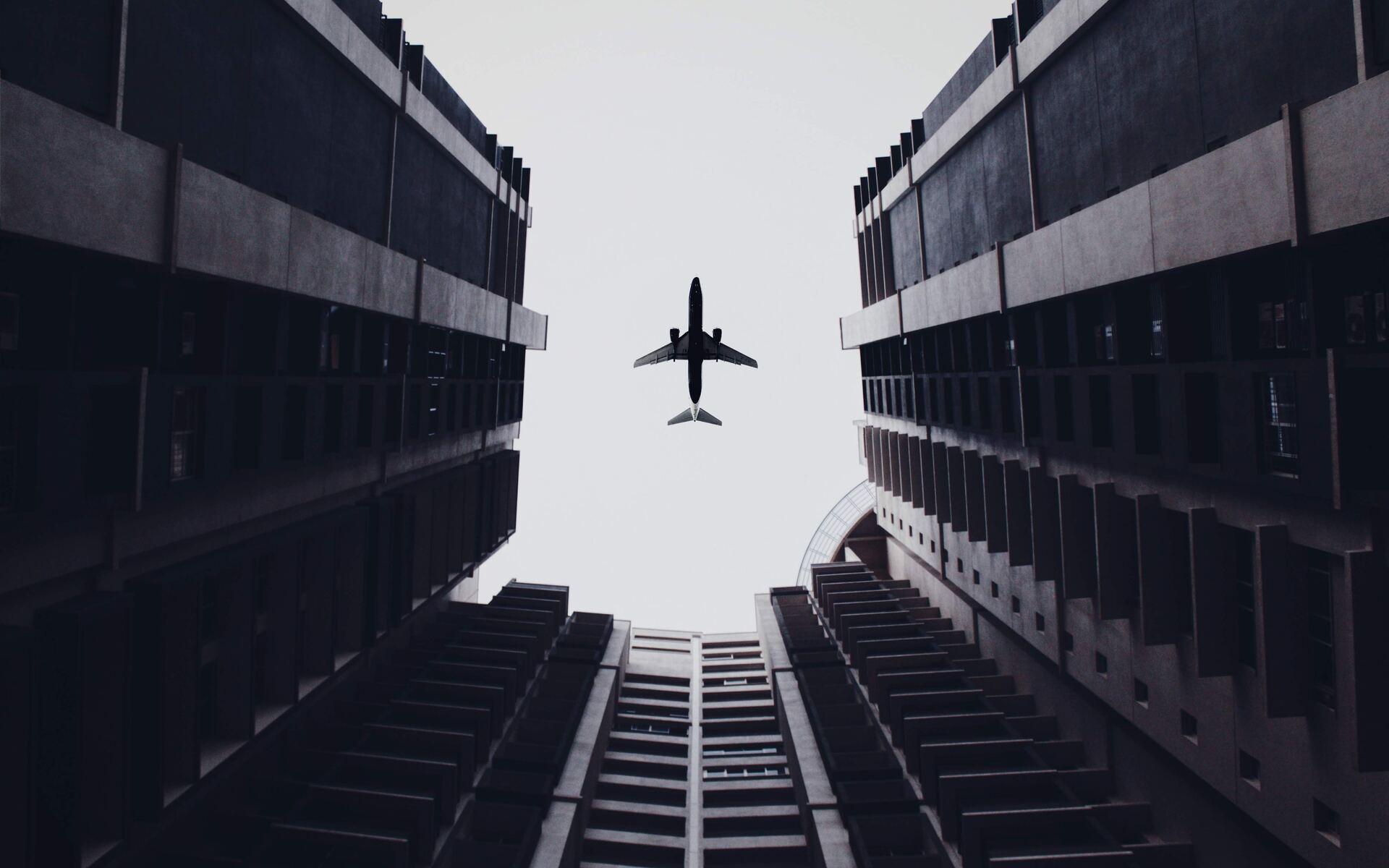 airplane-flying-above-the-buildings-5k-7t.jpg