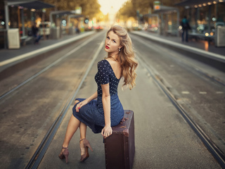 blonde-girl-sitting-suitcase-train-station-4k-88.jpg