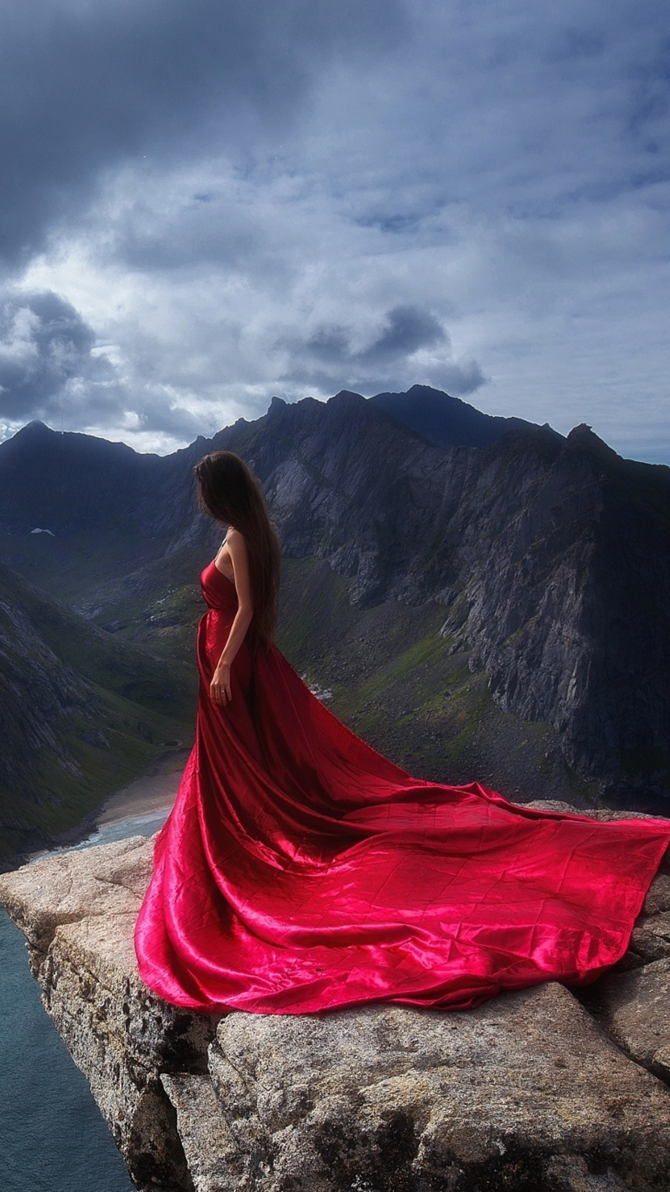 2160x3840 Girl In Red Dress Standing On The Edge Of Mountain Cliff