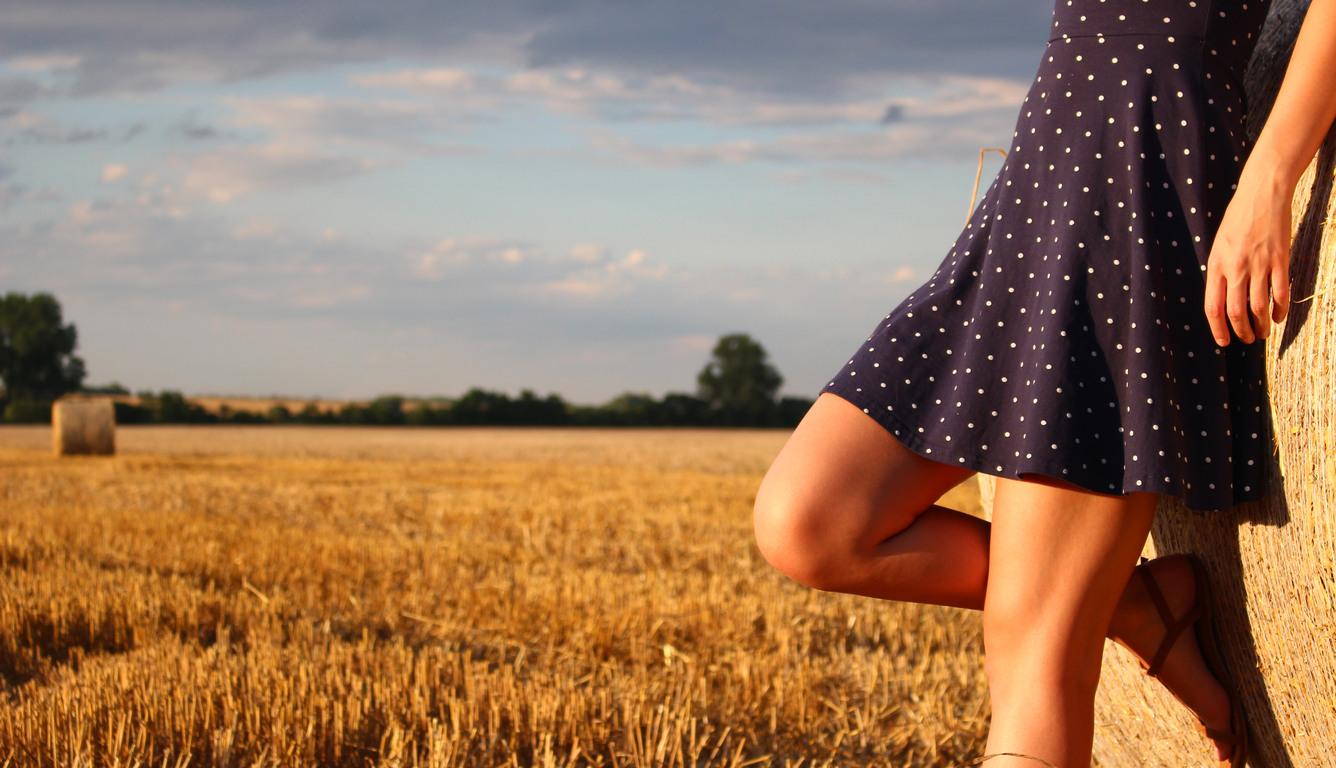 girl-standing-in-a-field-wearing-polka-dot-dress-fq.jpg