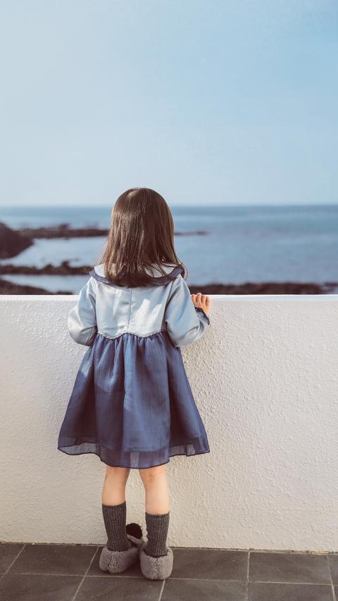 liitle-girl-holding-on-white-concrete-fence-ni.jpg