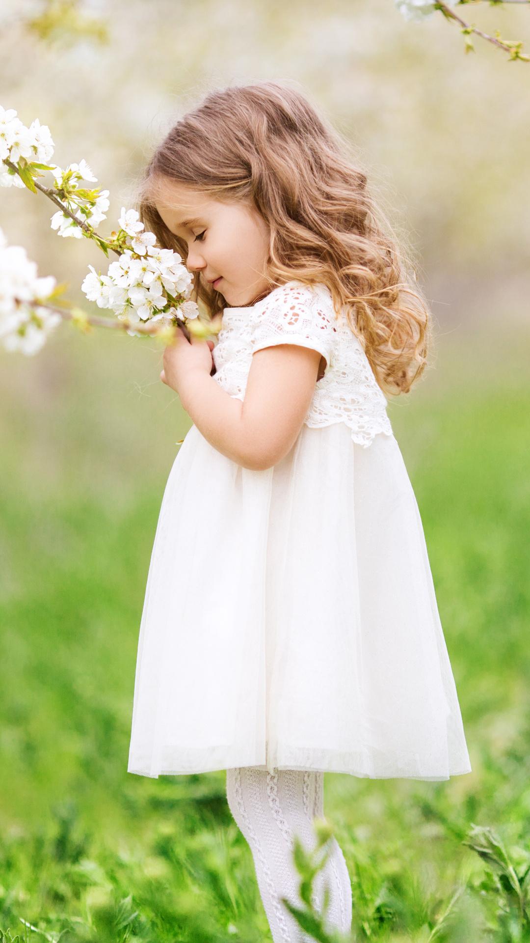 little-cute-girl-smelling-flowers-1k.jpg