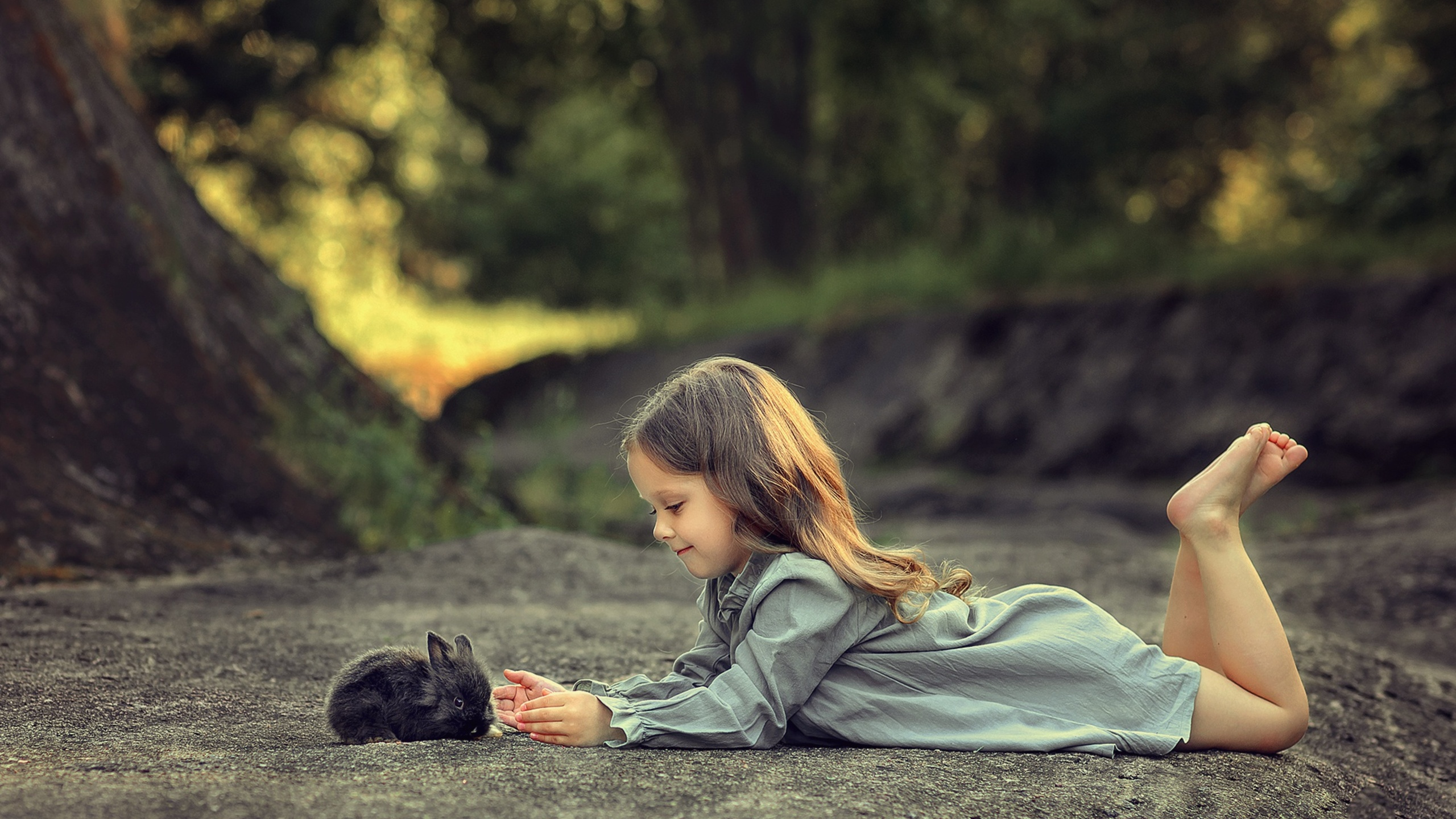 little-girl-lying-down-and-playing-with-rabbit-ez.jpg