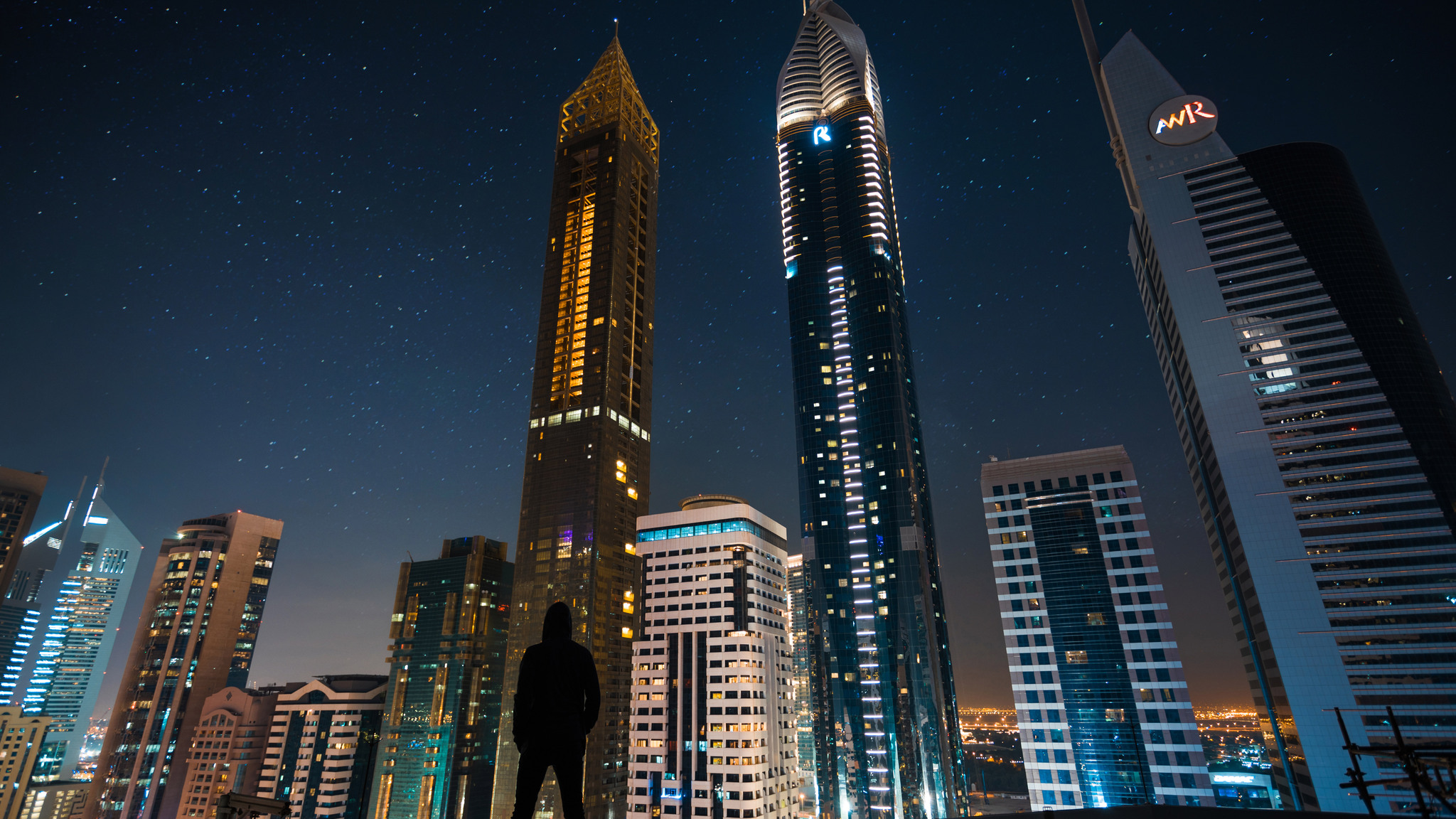 2048x1152 man standing front of tall buildings 2048x1152 resolution