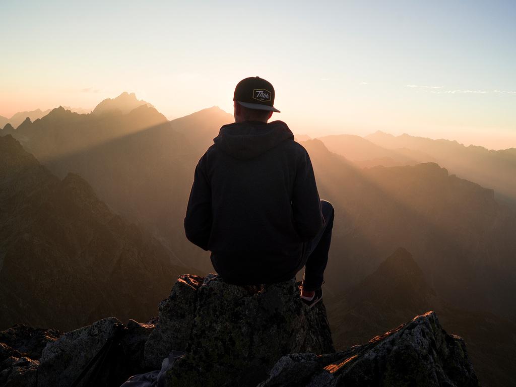 man-with-cap-sitting-on-the-mountain-edge-u6.jpg