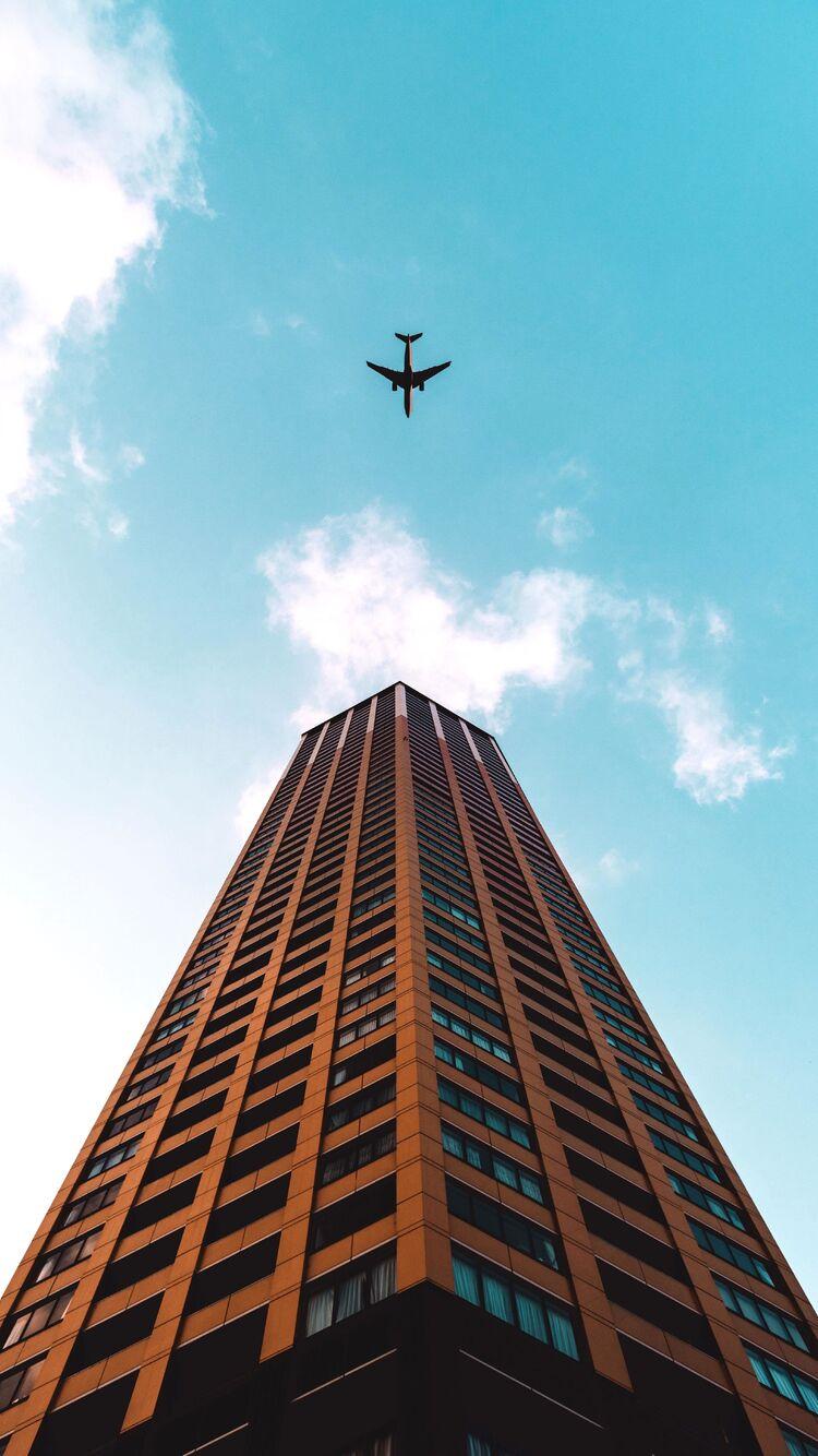 plane-flying-over-building-4k-gj.jpg