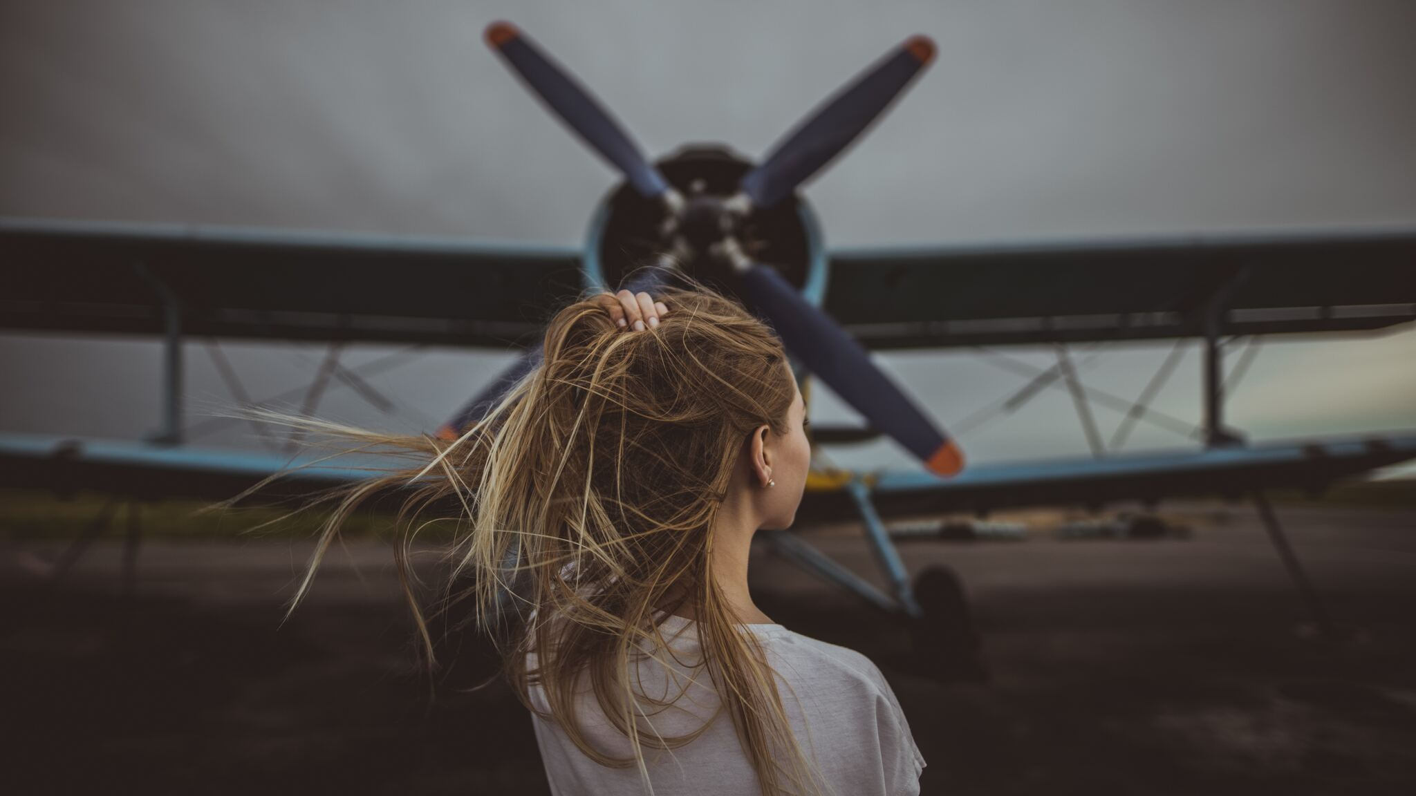 women-hands-in-hair-standing-in-front-of-plane-5k-oc.jpg