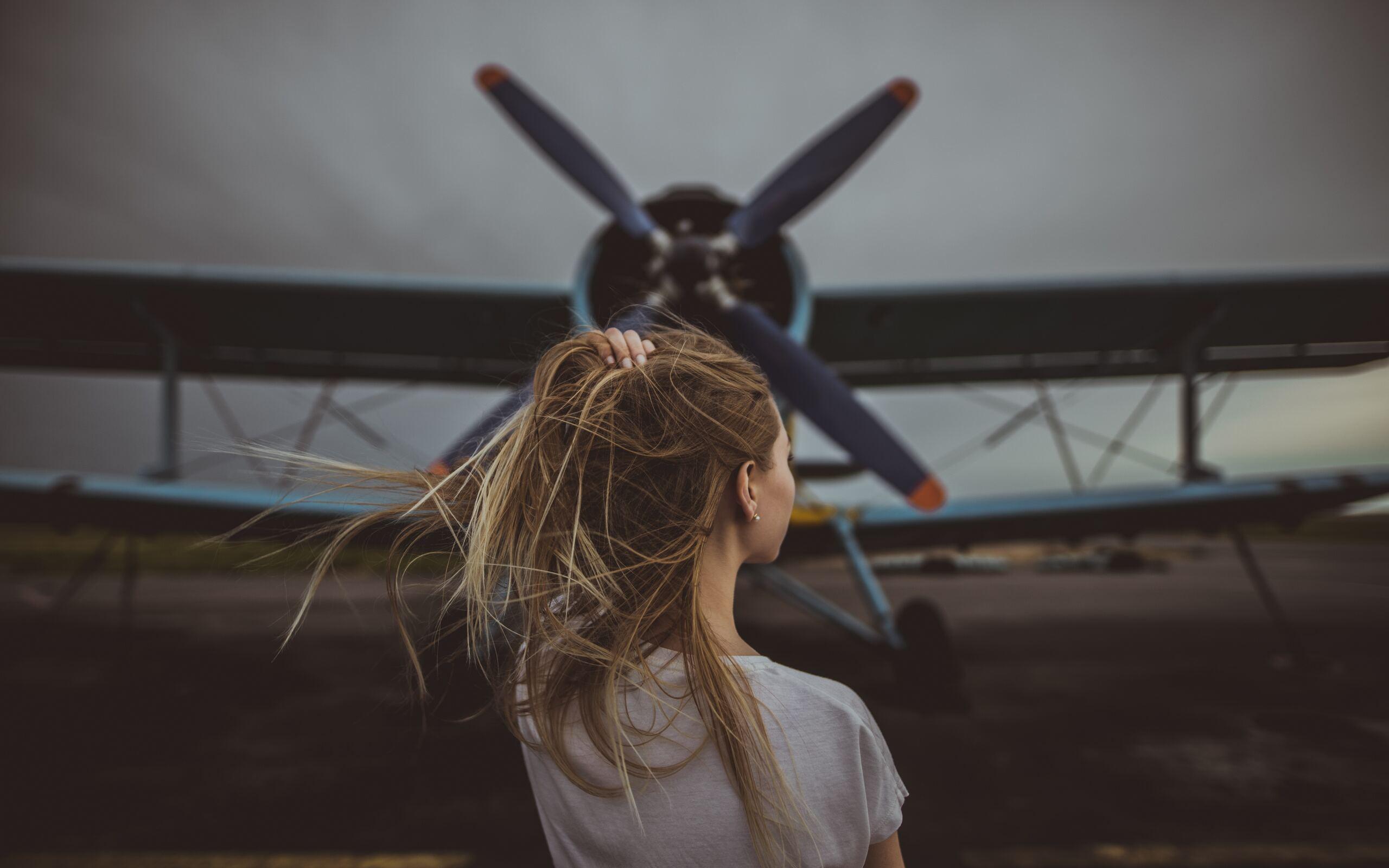 women-hands-in-hair-standing-in-front-of-plane-5k-oc.jpg