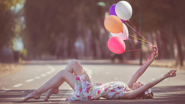 girl-with-balloons-in-hand-lying-down-road-v1.jpg