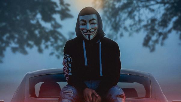 man-wearing-guy-fawkes-mask-while-sitting-on-car-4k-jw.jpg
