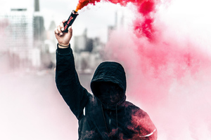 A Person In A Hoodie With Smoke Grenade