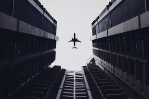 Airplane Flying Above The Buildings 5k Wallpaper
