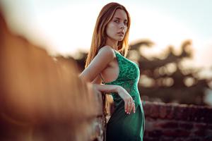Beautiful Girl Green Dress Leaning On Wall Wallpaper