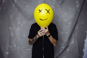Boy With Smiley Balloon On Face