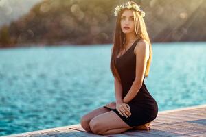 Brunette Girl In Black Dress Sitting At Pier Side