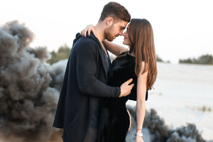 Cute Couple Black Clothing Beach Side Wallpaper