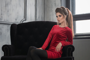 Girl In Red Dress Sitting On A Sofa Wallpaper