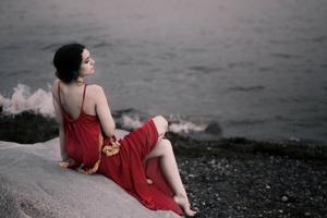 Girl In Red Dress Sitting On Rocks Beach 8k Wallpaper