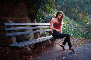 Girl Sitting On Bench Outdoors