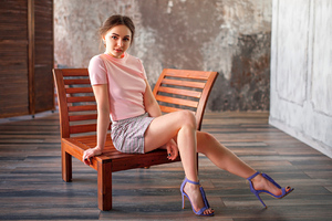 Girl Sitting On Chair Looking At Viewer Wallpaper