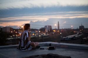 Girl Sitting On Rooftop Looking Towards Town 5k Wallpaper