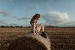 Girl Sitting On Straw Roll