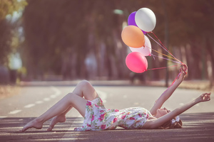 Girl With Balloons In Hand Lying Down Road Wallpaper