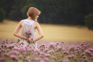 Girl With Flowers Standing In Field