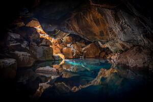 Iceland Cave Surrouned With Blue Body Of Water 5k Wallpaper
