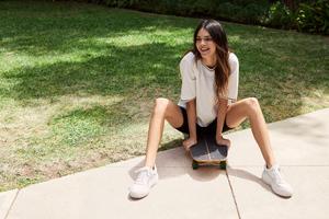Kendall Jenner Smiling Sitting On Skateboard Wallpaper