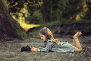 Little Girl Lying Down And Playing With Rabbit