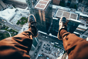Man Sitting On Top Of A Rooftop