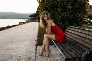 Model Sitting On Bench In Red Dress