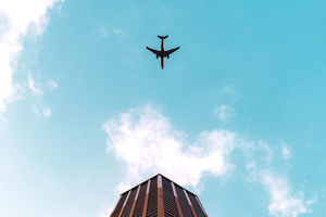 Plane Flying Over Building 4k Wallpaper