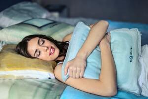 Woman Hugging A Blue Pillow