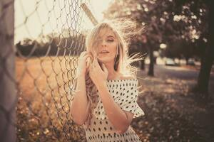 Woman Leaning On Chain Fence