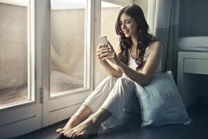 Woman Sitting Beside Window Holding Phone Wallpaper