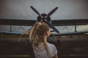 Women Hands In Hair Standing In Front Of Plane 5k Wallpaper