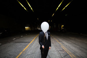 Young Man In Suit Holding Balloons In Front Of Face