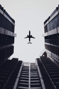 1440x2960 Airplane Flying Above The Buildings 5k