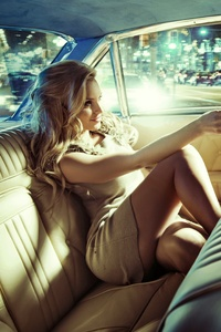Blonde Girl Sitting On Car Back Seat With Driver