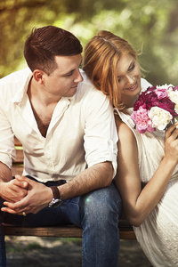 Couple Sitting On Bench With Flowers