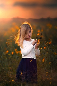 Cute Child Girl With Flowers Outdoors