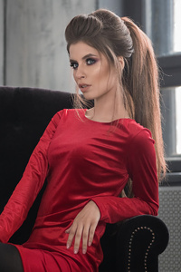 1080x2280 Girl In Red Dress Sitting On A Sofa