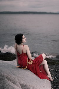 Girl In Red Dress Sitting On Rocks Beach 8k