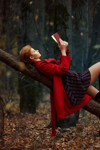 Girl Reading Book Lying On Back Outdoors