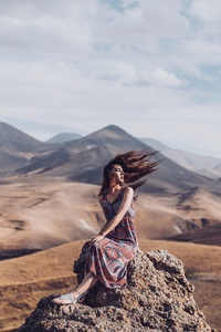 Girl Sitting On Rock Hairs In Air