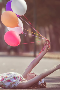800x1280 Girl With Balloons In Hand Lying Down Road