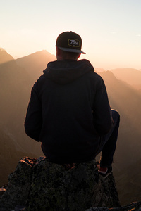 1440x2560 Man With Cap Sitting On The Mountain Edge